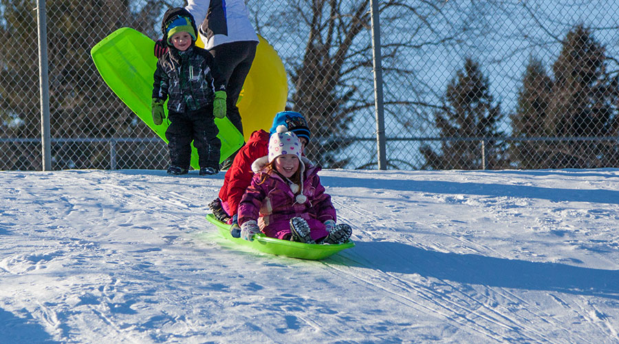 Kids sledding at Irons Park in West Branch, Michigan